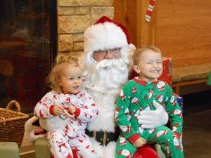 Children in PJs sitting on Santa's lap.